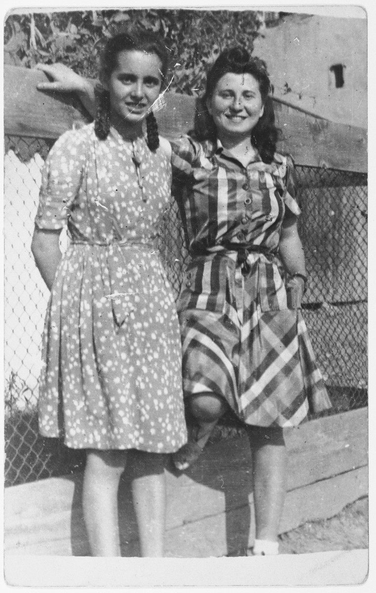 Anna Brunn and her friend Lili Gluck stand next to a fence.