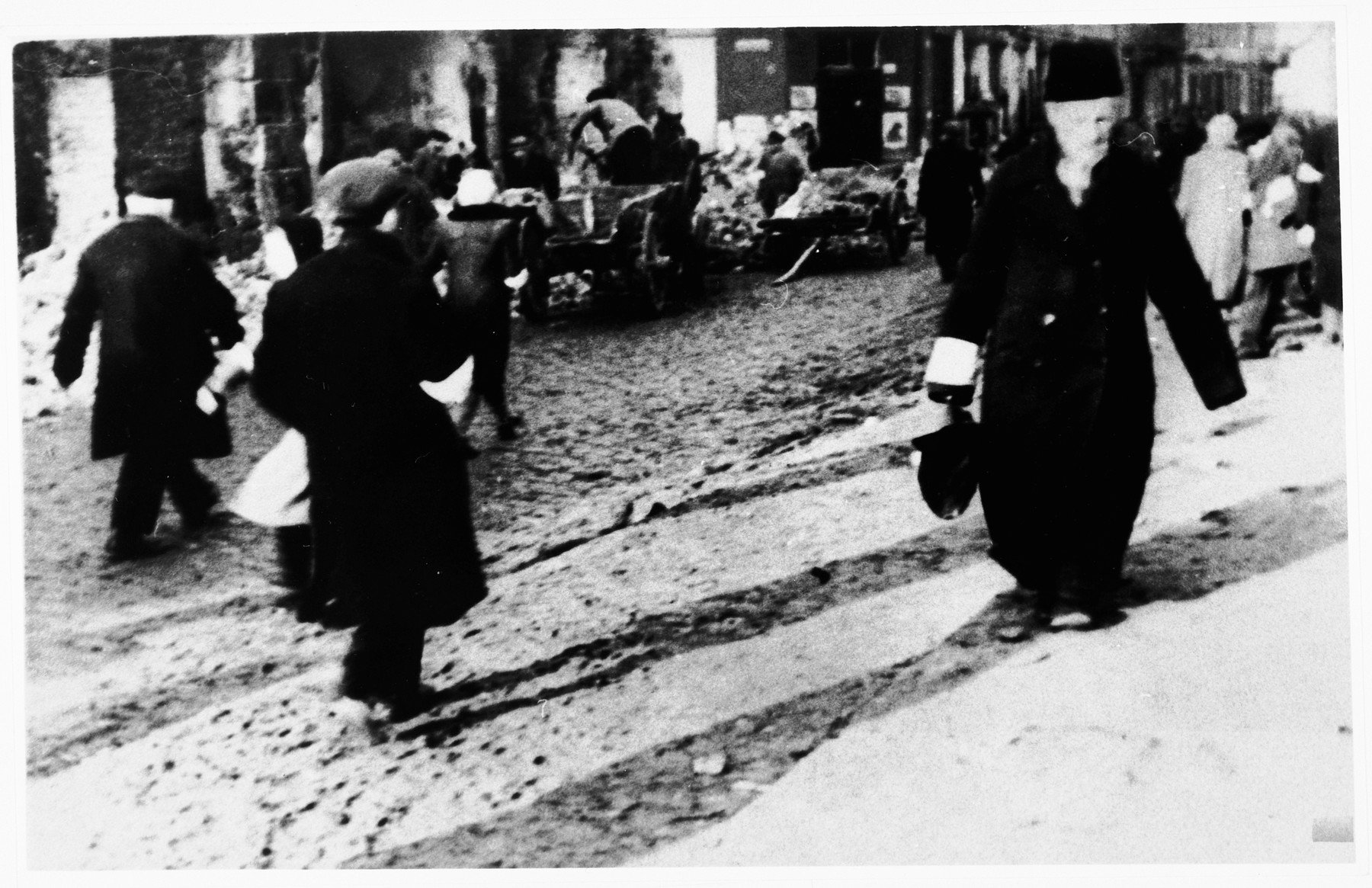 Jews wearing armbands walk along an unpaved street in an unidentified ghetto.
