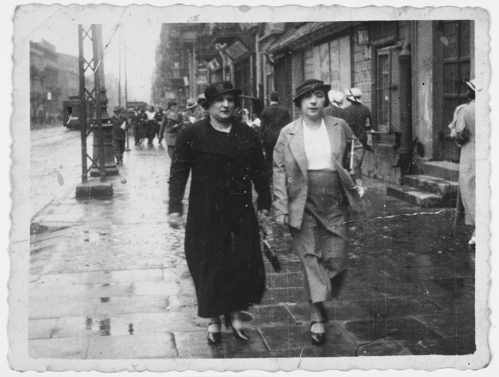 Bluma Shattan walks down a commercial street in Lodz with her sister-in-law Rivka