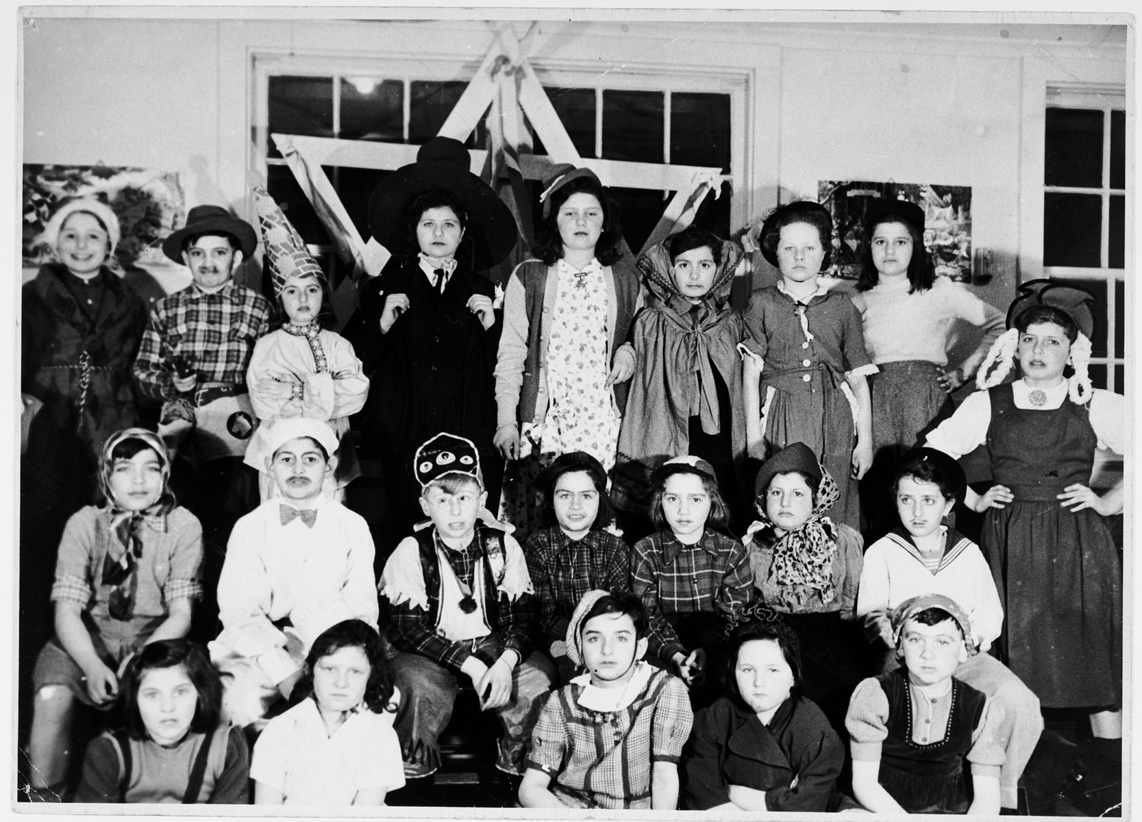Group portrait of children dressed in Purim costumes in the Fort Ontario refugee center.  Those pictured include Ray Harding, John Hirshler, Ruth Hendel, Walter Gruenberg and Willie Kramer.