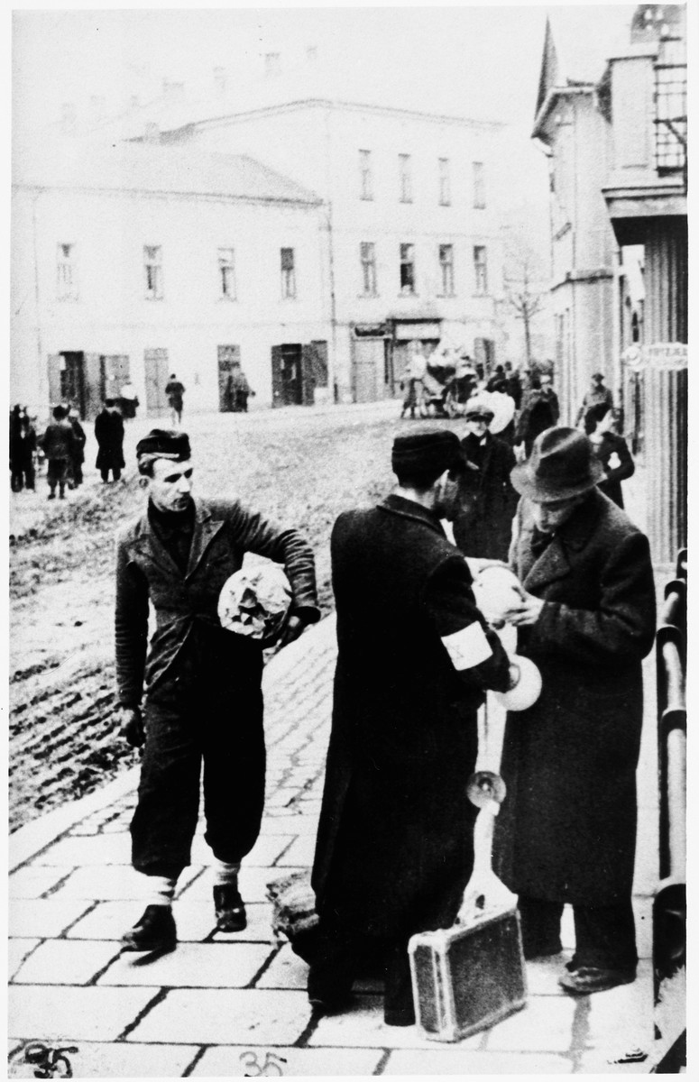 A vendor shows some of his belongings to a fellow Jew on the street of an unidentified ghetto.
