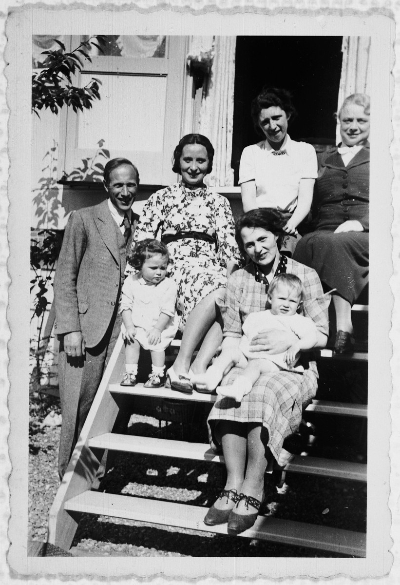 Rosemarie Schink sits on the steps to a house with a group of people including two of the Jews she hid in her attic, Lola and Lila.  Also pictured are Dr. Conrad Prager with his Christian wife, Betty and daughter, Irene.