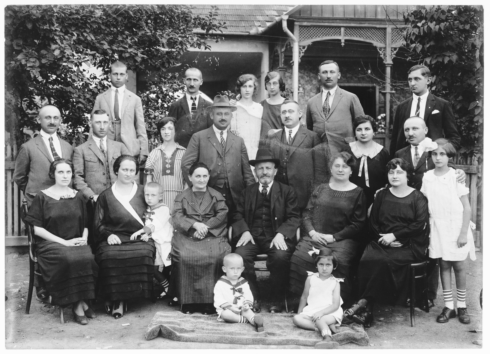 The extended Brunn family gathers in front of their home in Szendro Hungary.  Seated in front are two children: Laci Blumberger and Margit Brunn.  Front row (left to right) are Szofi Furth Brunn, Margit Brunn Blumberger, Hermina Reichmann Brunn, Mor Brunn, Imre Blumberger, Mrs. Ignacz Brunn and Hermine Brunn.  Second row: Wilmos Brunn, Sandor Blumberger, Mrs. Jozef Brunn, Samu Brunn, Ignacz Brunn, Rozsi Brunn and Haim Brunn.  Top row: Gyula Neuman, Jozef Brunn, Jolan Brunn, ? Brunn and Jajos Brunn.