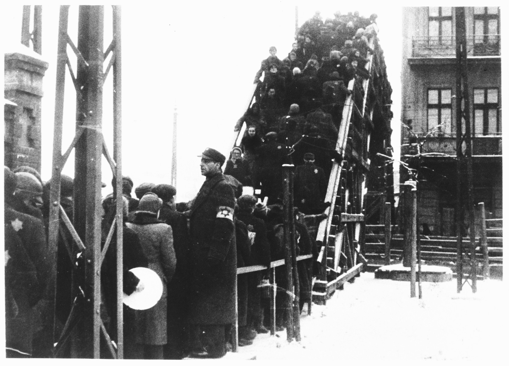 A Jewish policeman stands guard while Lodz ghetto residents wait in line to cross one of the pedestrian bridges.