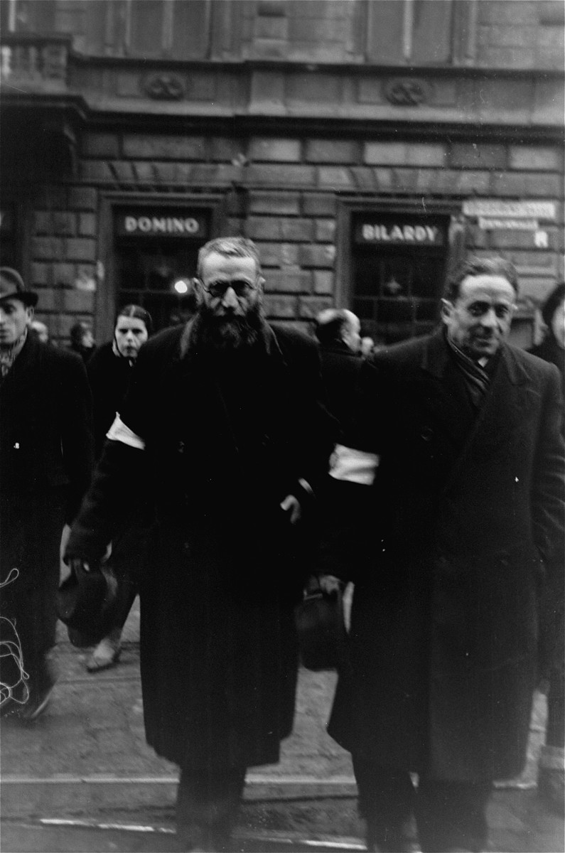 Jews crossing Chlodna Street in the Warsaw ghetto doff their hats to the photographer, in accordance with the German order requiring Jews to remove their hats in the presence of German personnel.