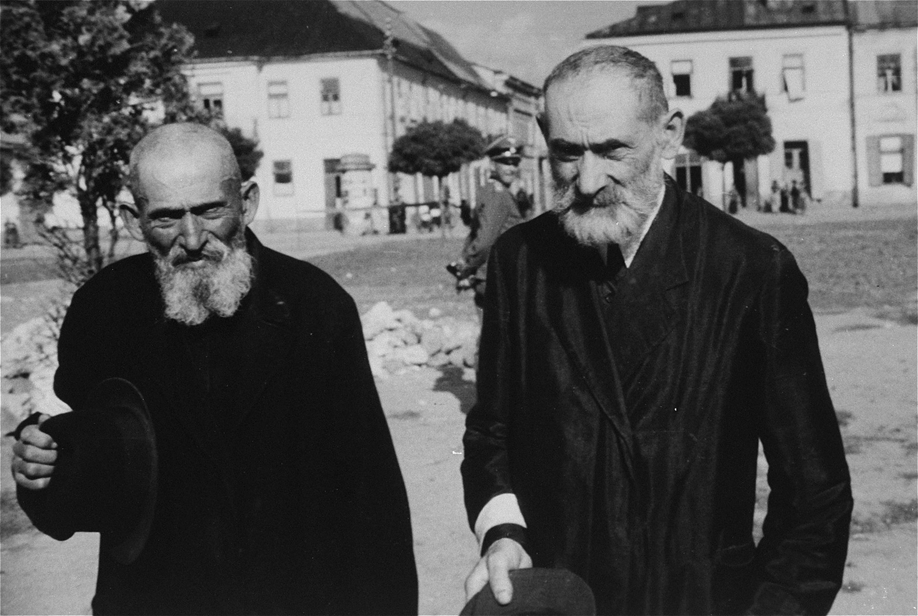 Two religious Jews wearing armbands are forced to remove their hats on a street in an unidentified ghetto.    An SS officer is visible in the background.