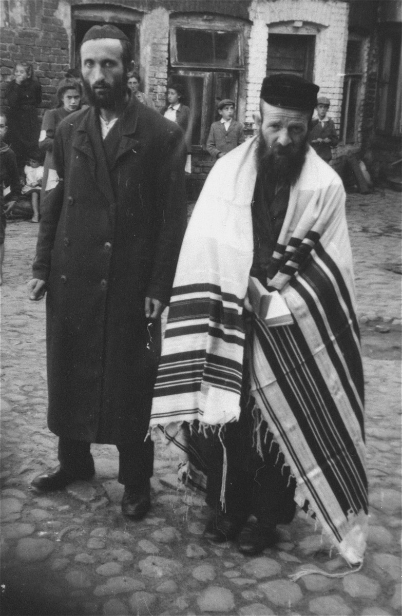 Two religious Jews are forced to pose in a public square in an unidentified ghetto.  The man at the right wears a prayer shawl.    The photograph was likely taken by a member of the SS, probably in the first full year of the German occupation, before the establishment of the ghetto.  German personnel tended to photograph Jews, especially religious Jews, in ghettos in Poland due to their appearance, which was considered unique.