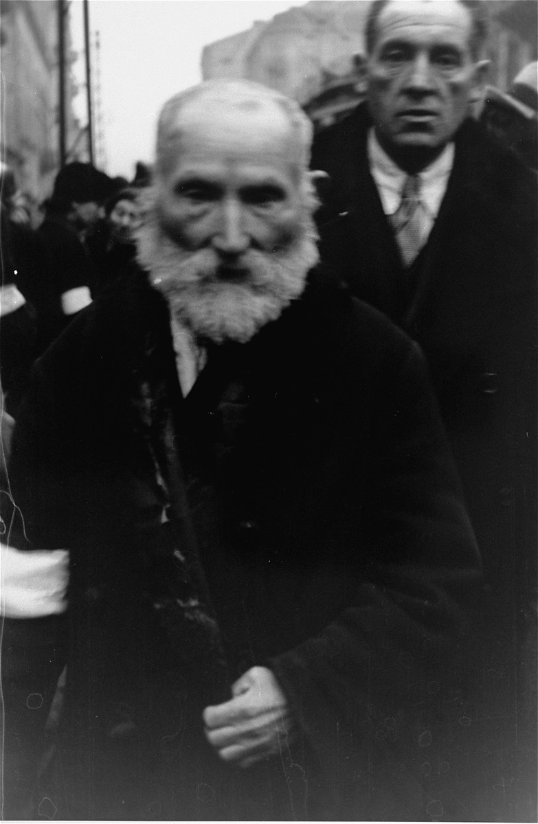 Jewish men on the street in the Warsaw ghetto doff their hats to the photographer, in accordance with the German order requiring Jews to remove their hats in the presence of German personnel.