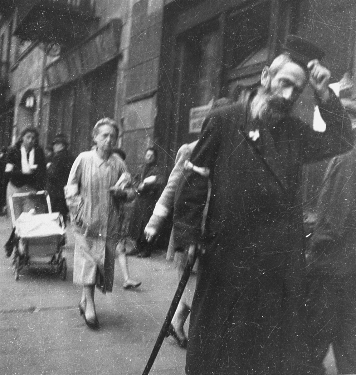 "A Jewish man on the street in the Warsaw ghetto doffs his hat to Heinrich Joest (the photographer) in accordance with a humiliating order that Jews remove their hats in the presence of German personnel.    Joest's original caption reads: ""This old man took his hat off in front of me as I was photographing him.  This happened to me several times because the Jews had been ordered to do it."""