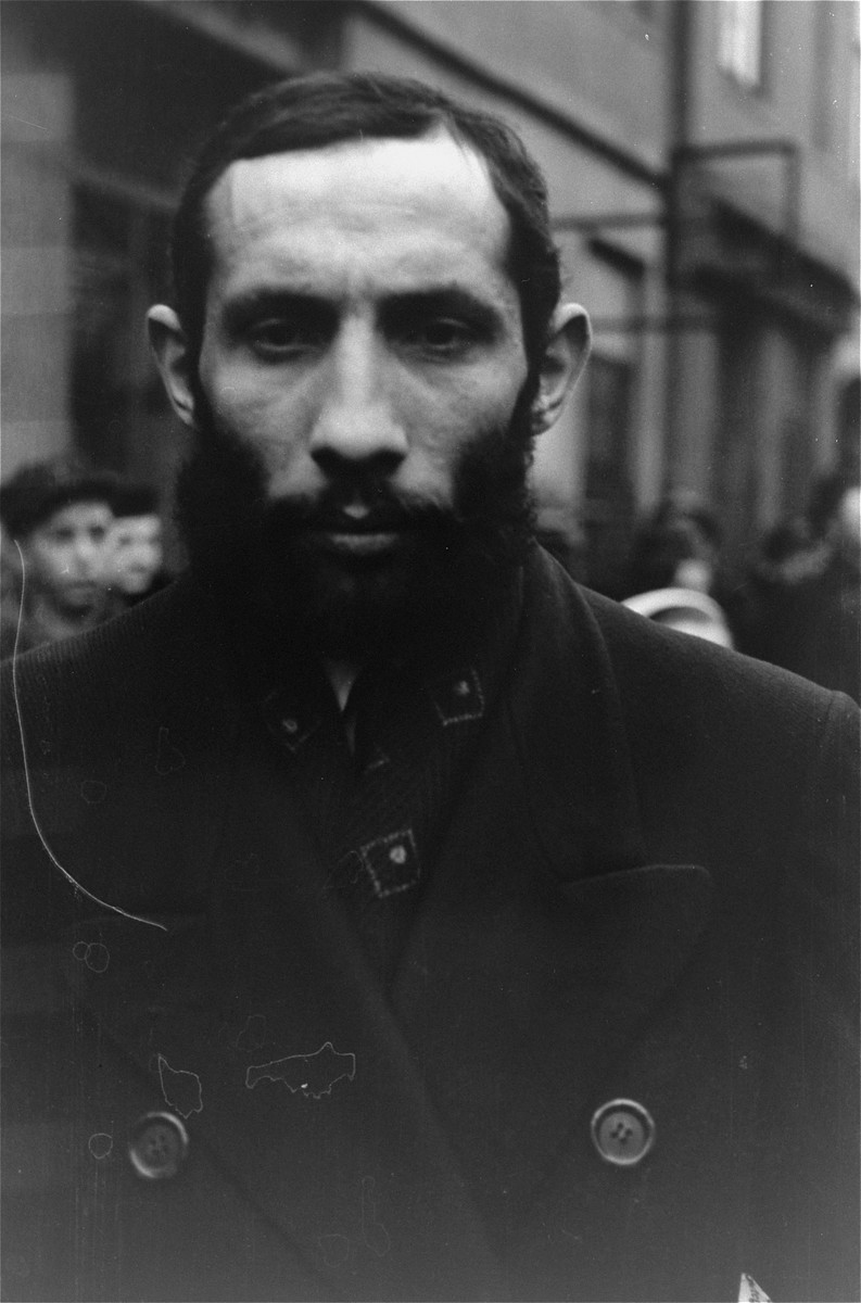 A Jew in the Warsaw ghetto stands bare-headed after having removed his hat before the German photographer, in accordance with the German order requiring Jews to remove their hats in the presence of German personnel.