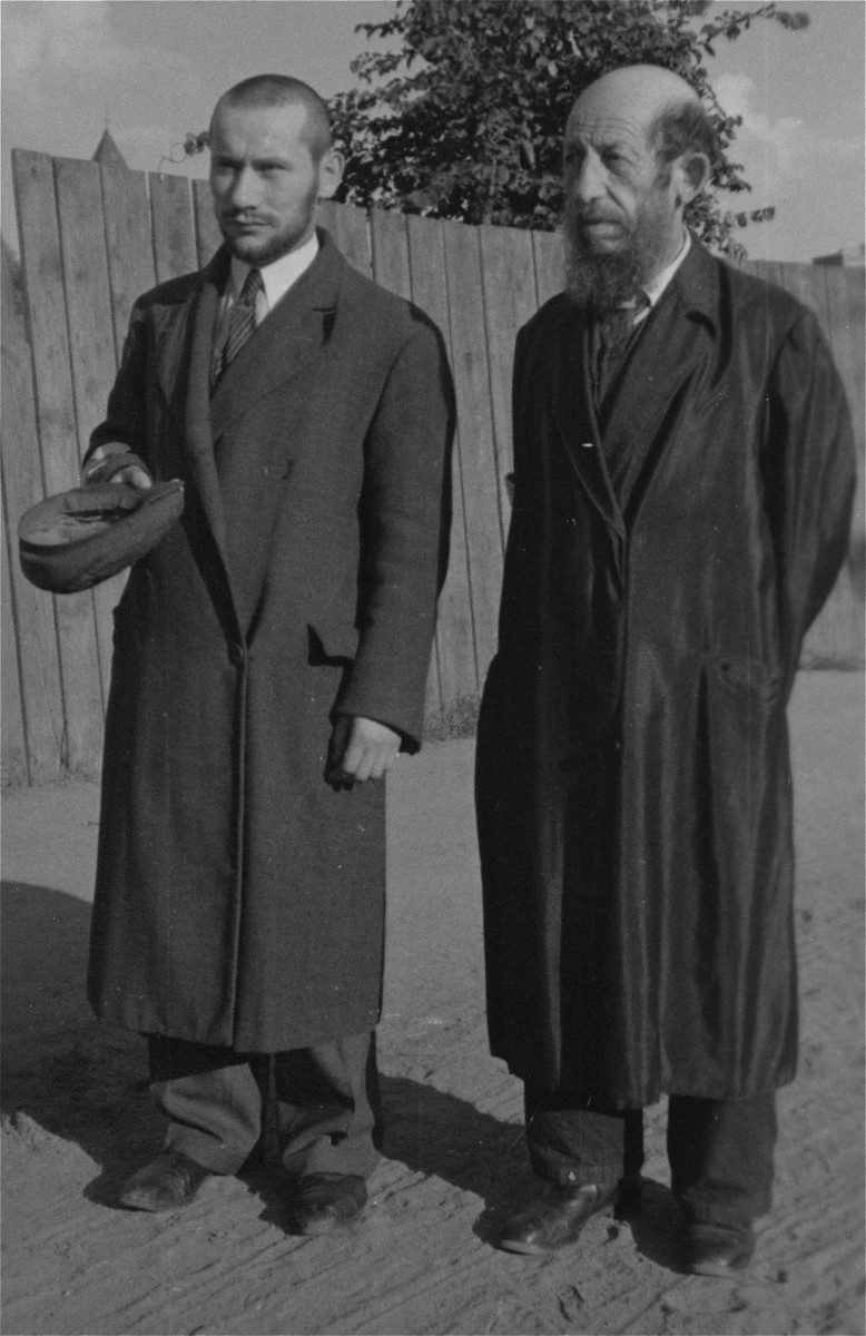 Two religious Jews are forced to remove their hats in an unidentified ghetto.