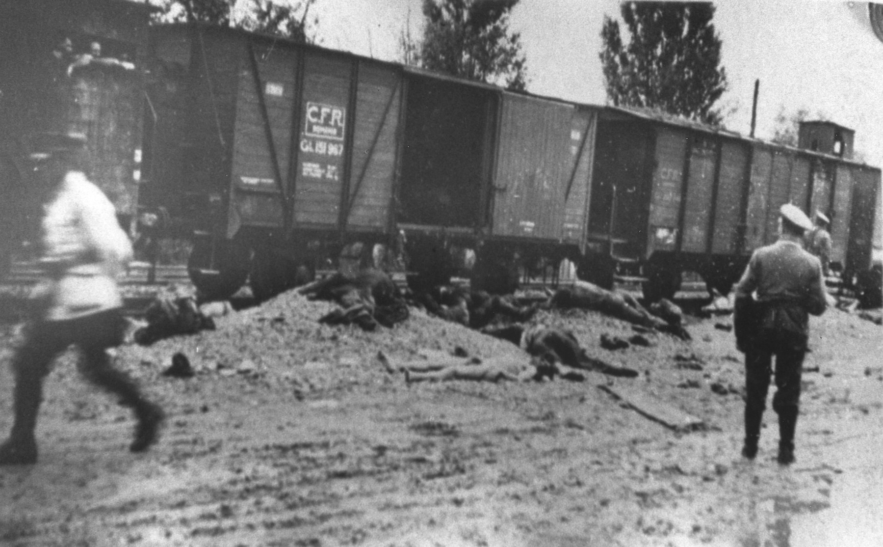 Romanian police walk past the bodies of Jews removed from the Iasi-Calarasi death train in Targu-Frumos.
