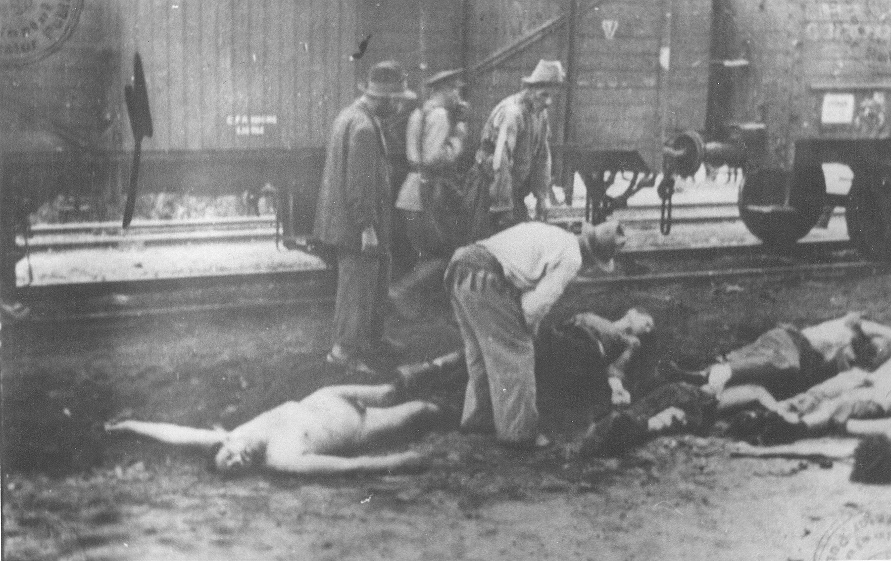 A Romanian guard walks past Gypsies removing bodies from the Iasi-Calarasi death train during a stop in Targu-Frumos.
