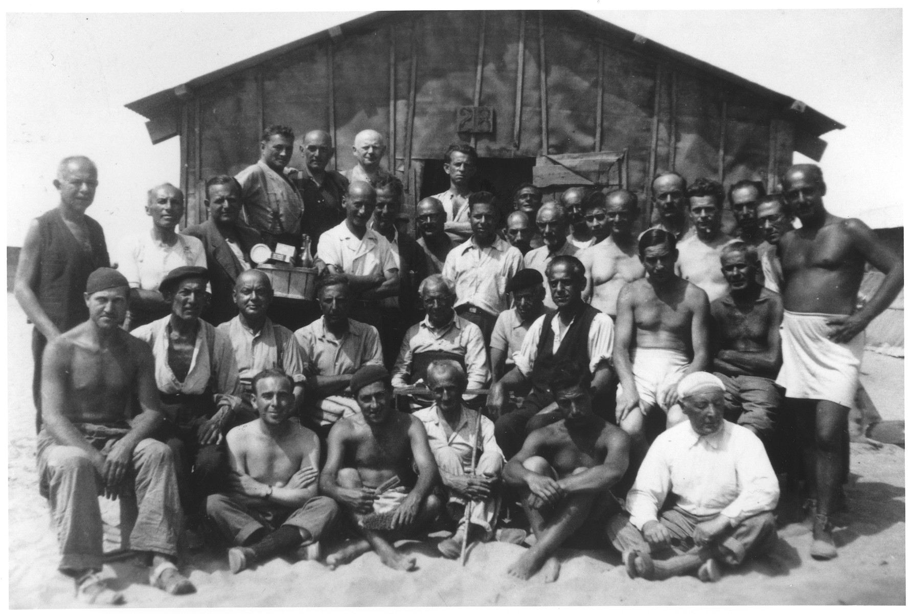 A group of male prisoners poses outside barrack no. 28 in the Saint Cyprien internment camp.  The man in the top row, second from the right is Moritz Adler.