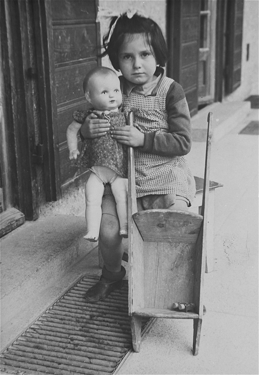 A young Jewish DP girl poses with a doll and toy stroller in the Feldafing displaced persons camp.  Pictured is Reisele Kirkel.