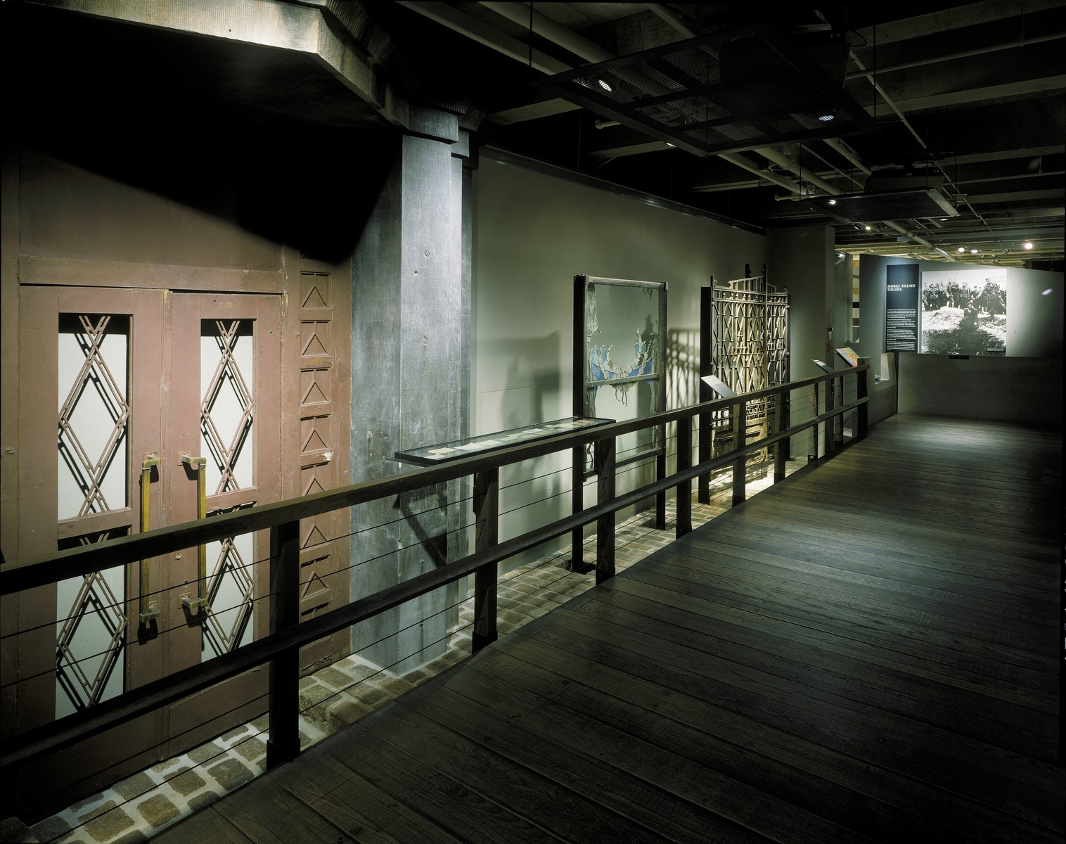 View of the ghetto bridge installation on the third floor of the permanent exhibition at the U.S. Holocaust Memorial Museum.   This view includes the door of the Lodz ghetto hospital, the window of the Kracow synagogue, the gate to the Jewish cemetery in Tarnow, and the mobile killing squad mural.