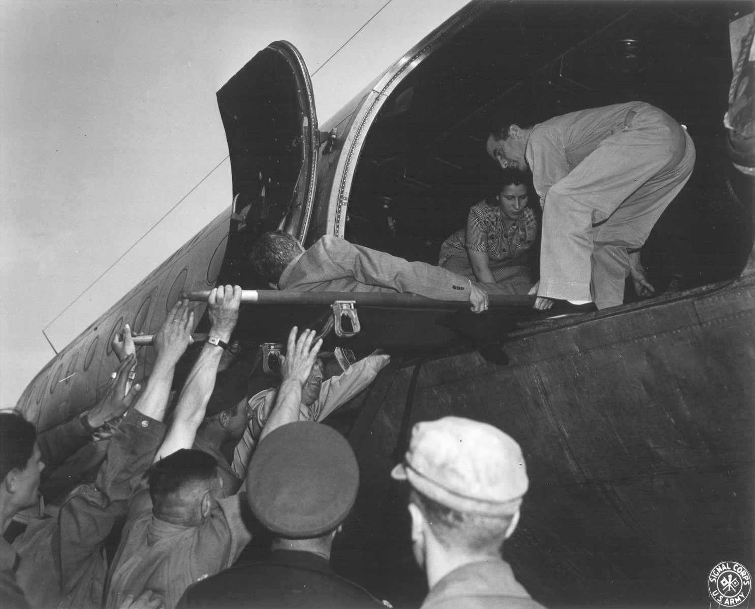 A Jewish DP who is being evacuated to Frankfurt am Main during the Berlin Blockade, is lifted on a stretcher and placed in an airplane.