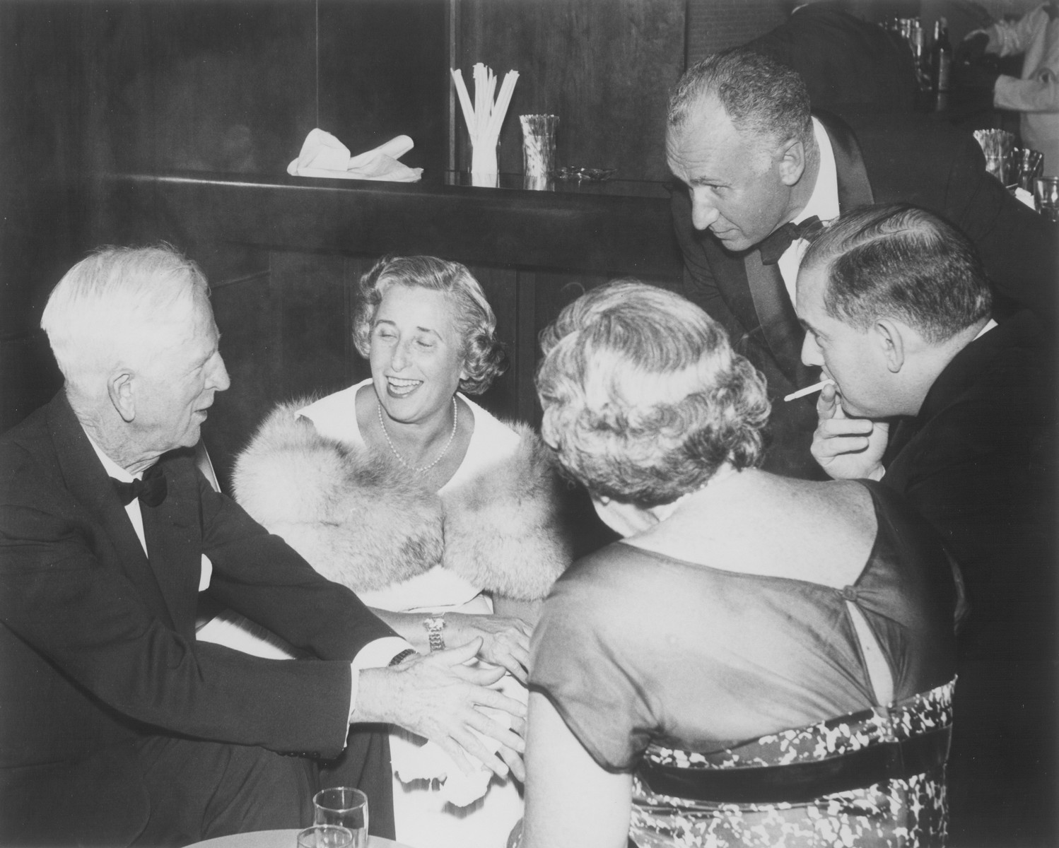 American Jewish philanthropist Abraham S. Kay speaks to James G. McDonald and others at an affair in Washington, D.C.  Among those pictured are: James G. McDonald (left), Abraham S. Kay (top right) and Abraham Harman (far right with cigarette).