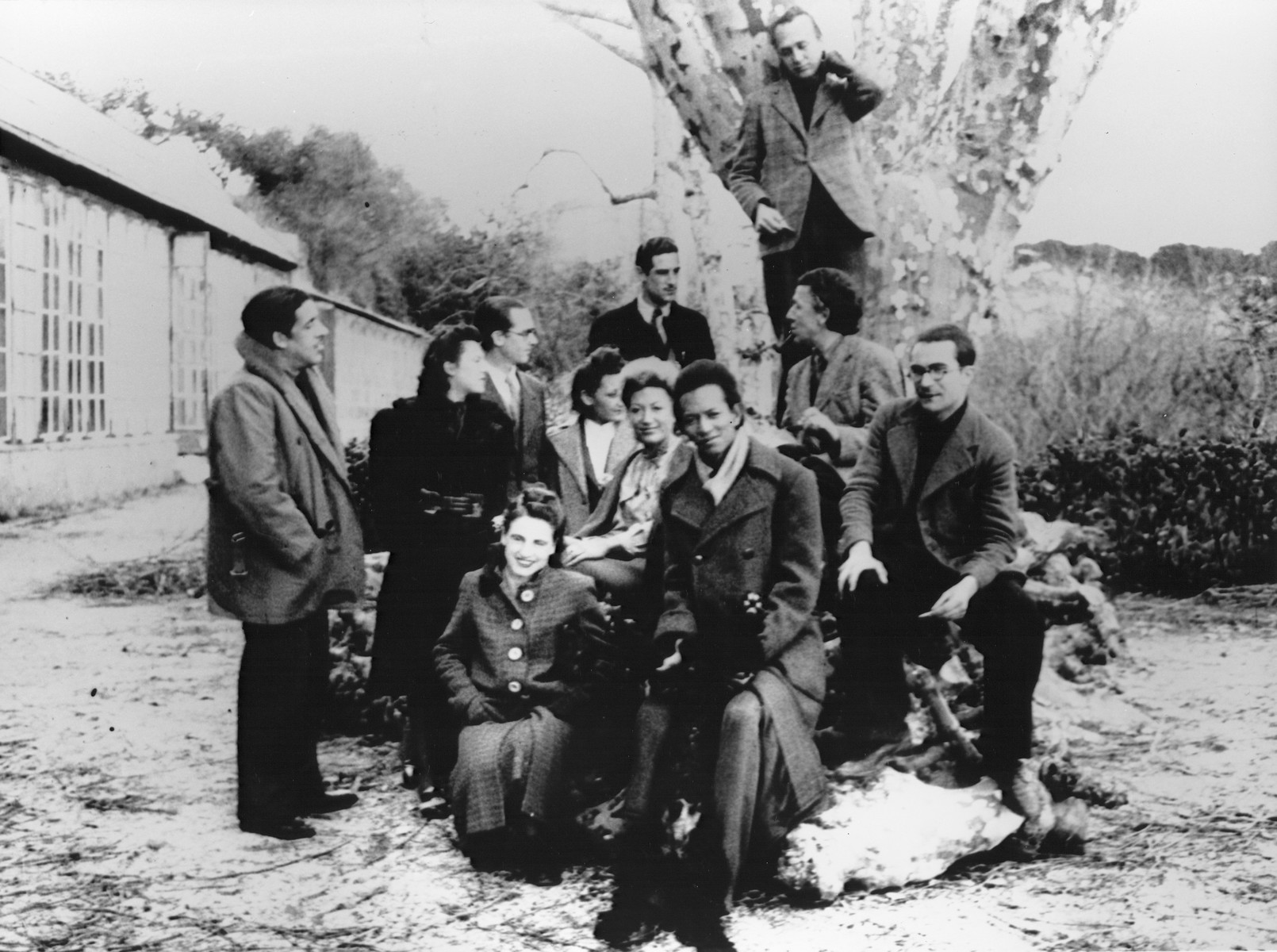 A group of artists poses on the grounds of the Villa Air-Bel near Marseilles.  Among those pictured are Jacques Herold, Oscar Dominguez, Andre Breton, Jacqueline Lamba Breton, Jacques Herold, and Wifredo and Helene Lam.