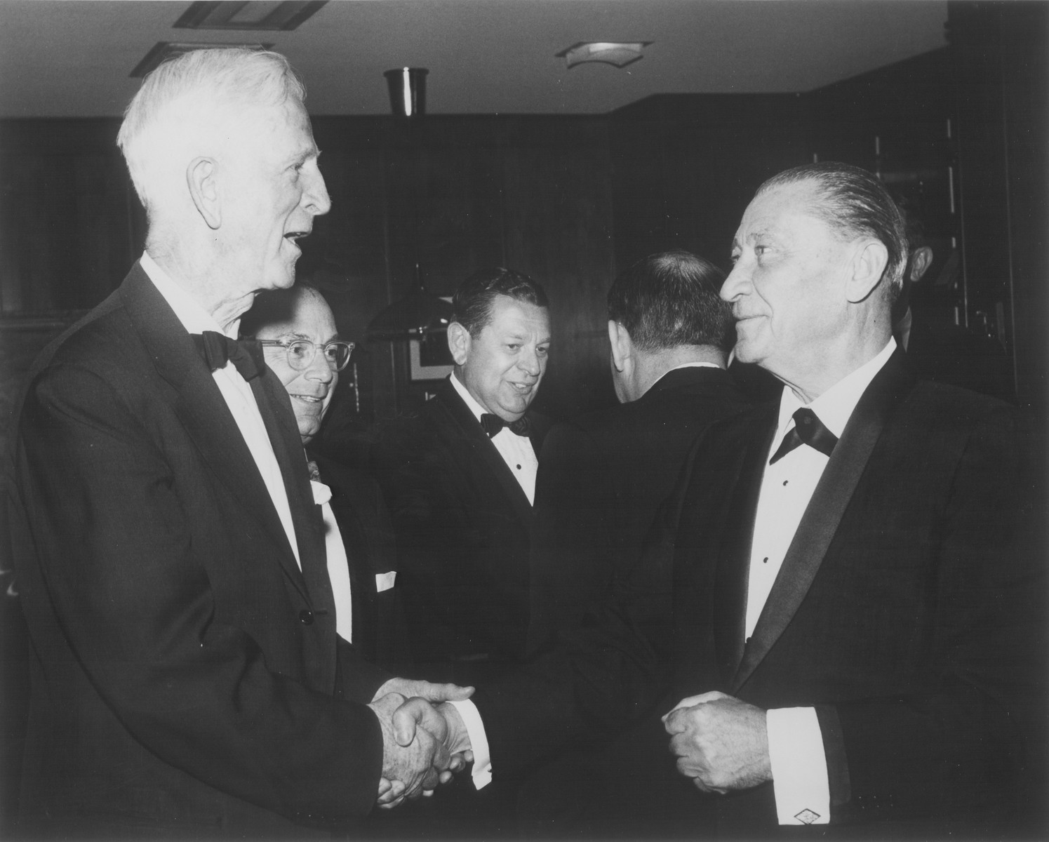 American Jewish philanthropist Abraham S. Kay (right) shakes hands with James G. McDonald (left) at an affair in Washington, D.C.  Pictured from left to right are: James G. McDonald, unknown, Stanley Weiner, Abraham Harman, and Abraham S. Kay.