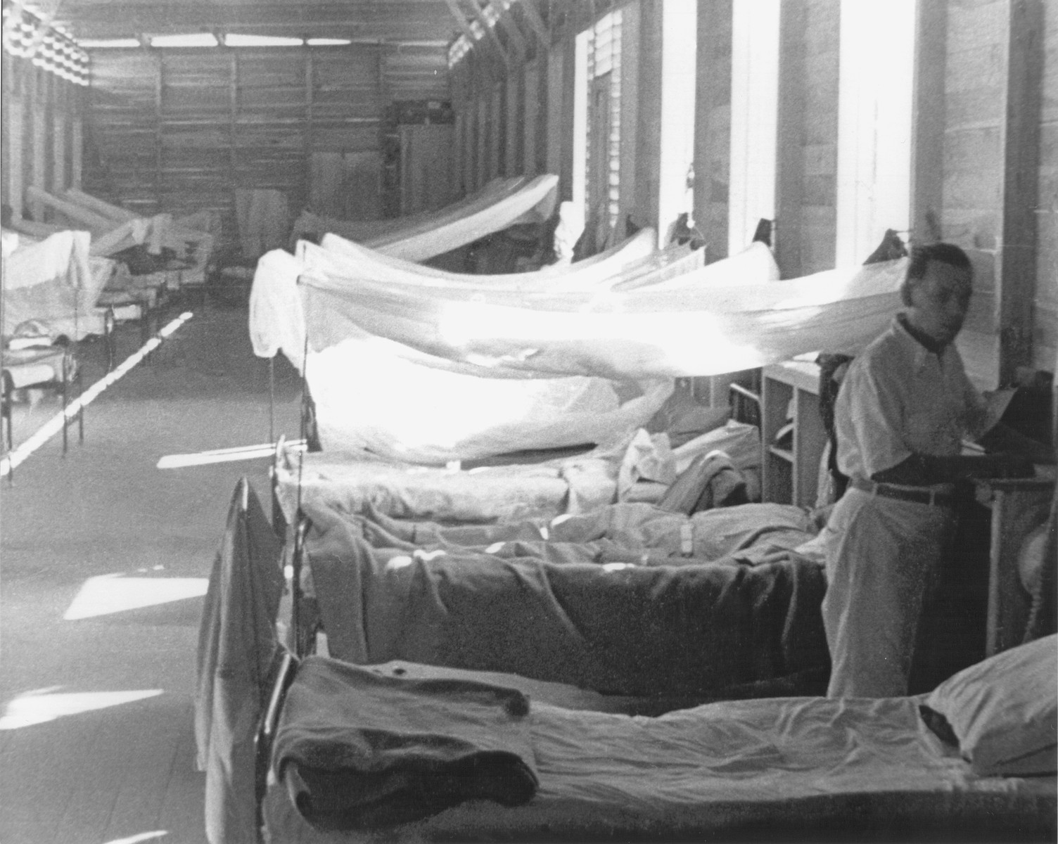 A Jewish refugee stands between two cots in the men's barracks at the Sosua settlement.
