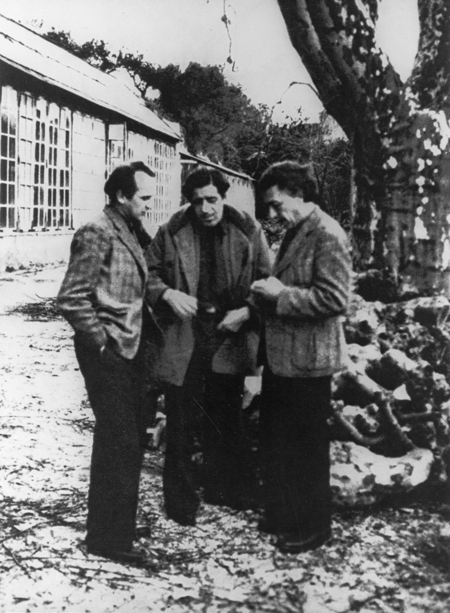 Three artists converse on the grounds of the Villa Air-Bel near Marseilles.  Pictured from left to right are: Jacques Herold, Oscar Dominguez and Andre Breton.