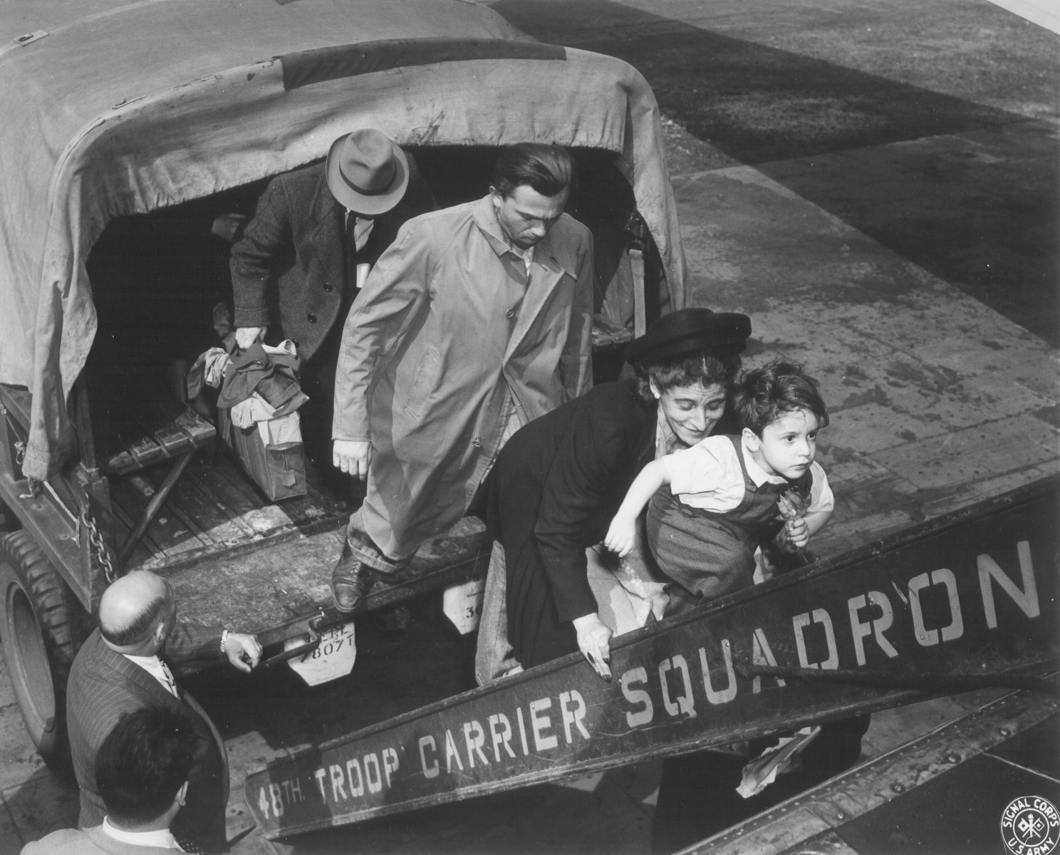 Jewish DPs who are being evacuated to Frankfurt am Main during the Berlin Blockade, walk off the back of a  truck and onto the steps of an airplane.