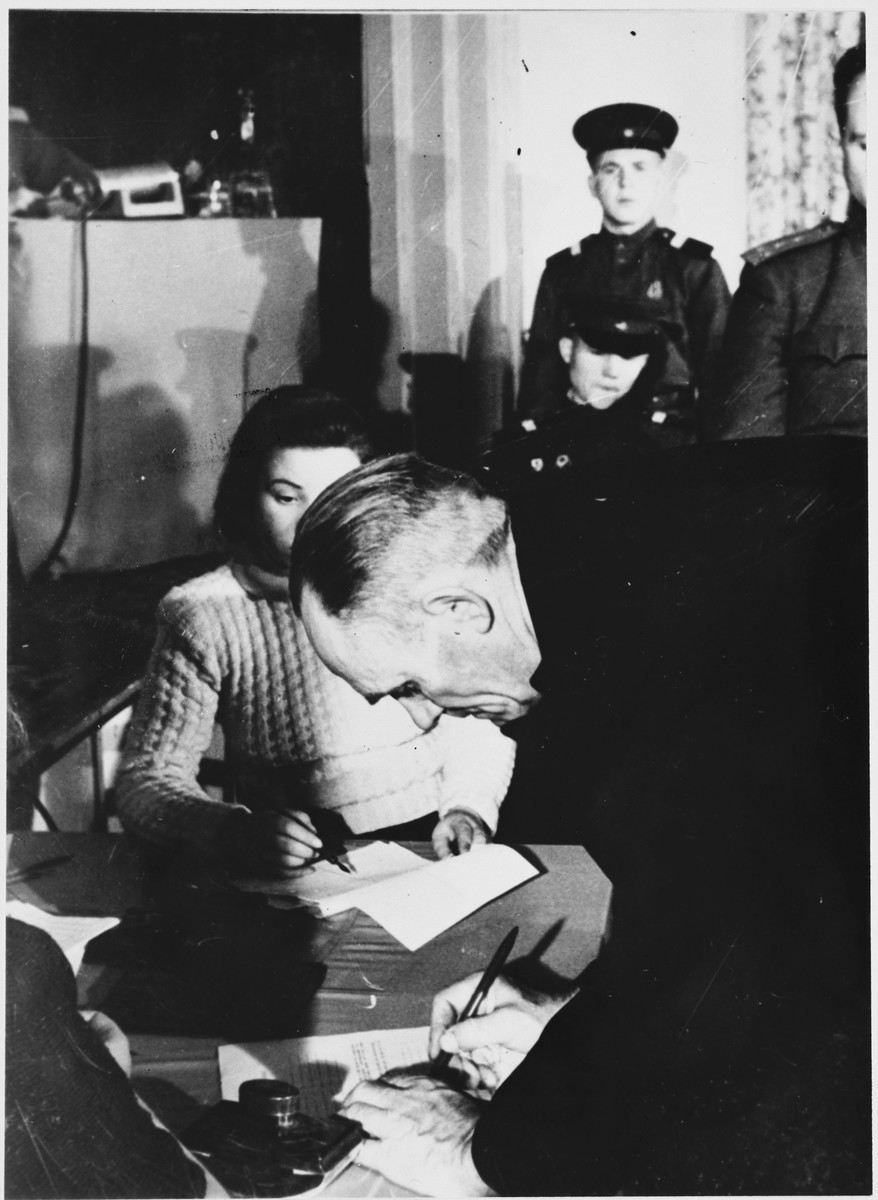 An unidentified man signs a document at the Sachsenhausen concentration camp war crimes trial in Berlin.