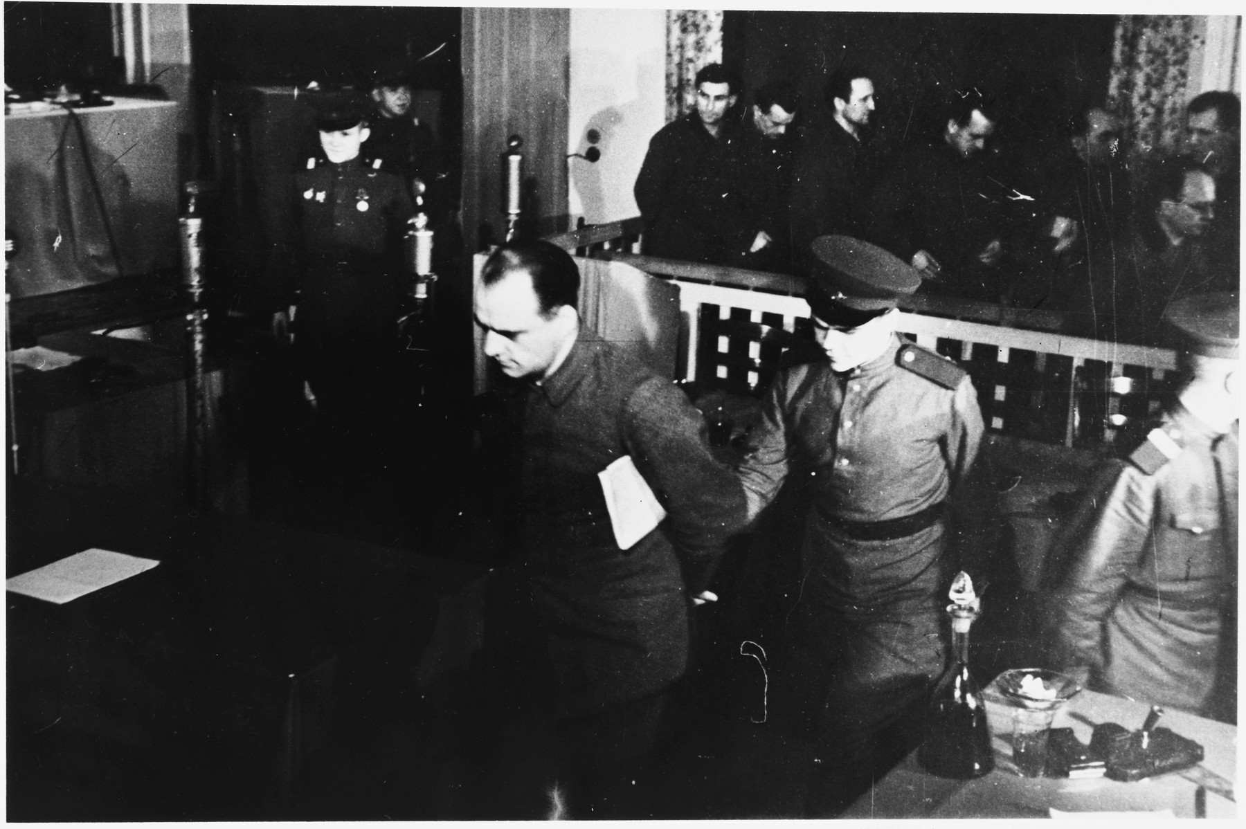 Defendant Ludwig Rehn is led out of the dock at the Sachsenhausen concentration camp war crimes trial in Berlin.