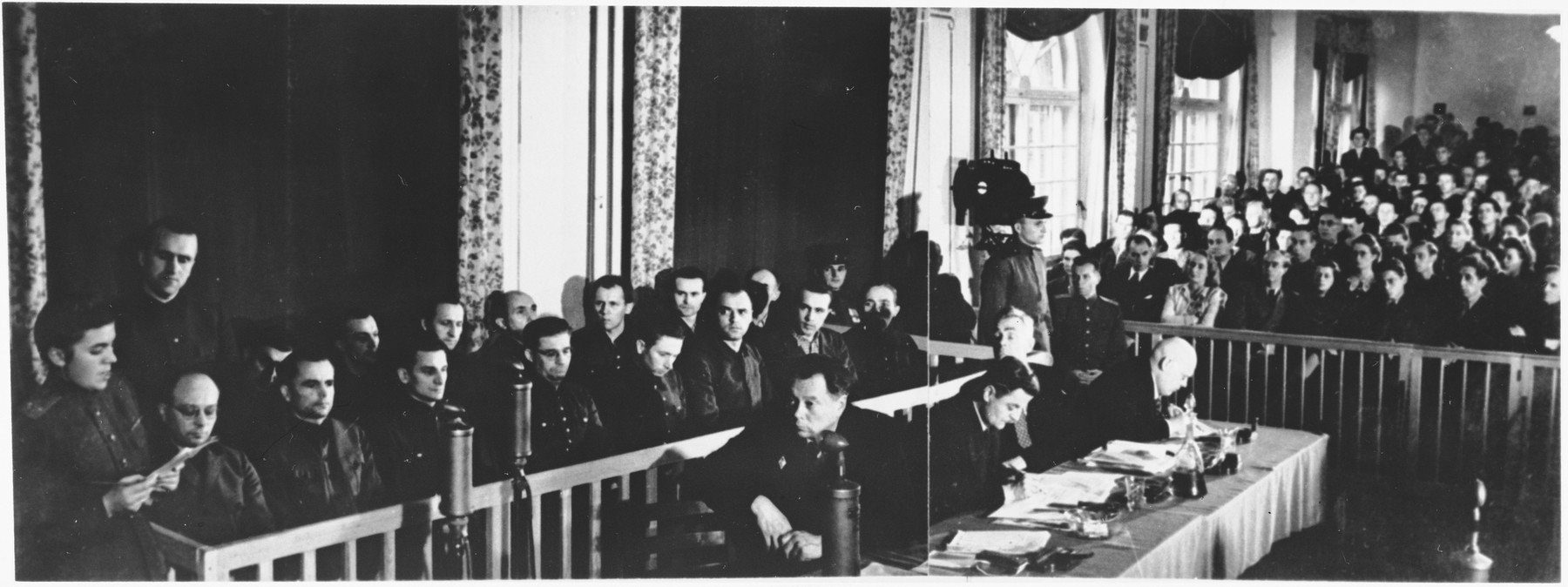 View of the courtroom at the Sachsenhausen concentration camp war crimes trial in Berlin.  The defendants are pictured at the left, their lawyers in the middle, and spectators at the right.