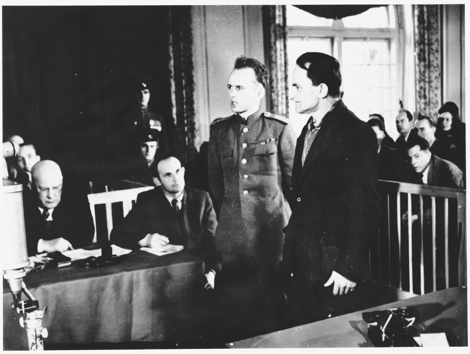 A witness is introduced at the Sachsenhausen concentration camp war crimes trial in Berlin.  Among those pictured it Ewald Becker (dark suit, to the right of the Russian officer).