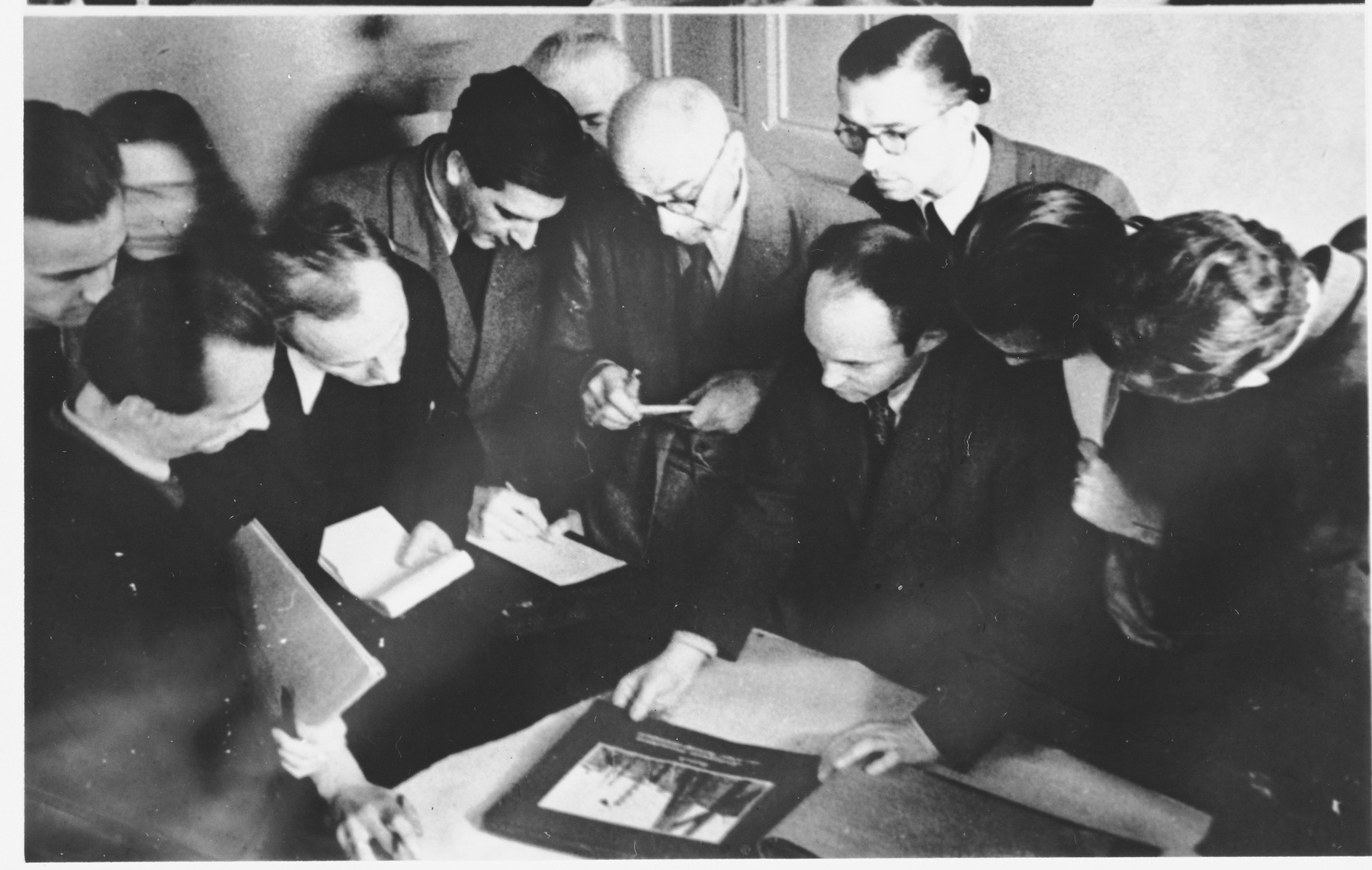 Court reporters examine a piece of evidence at the Sachsenhausen concentration camp war crimes trial in Berlin.