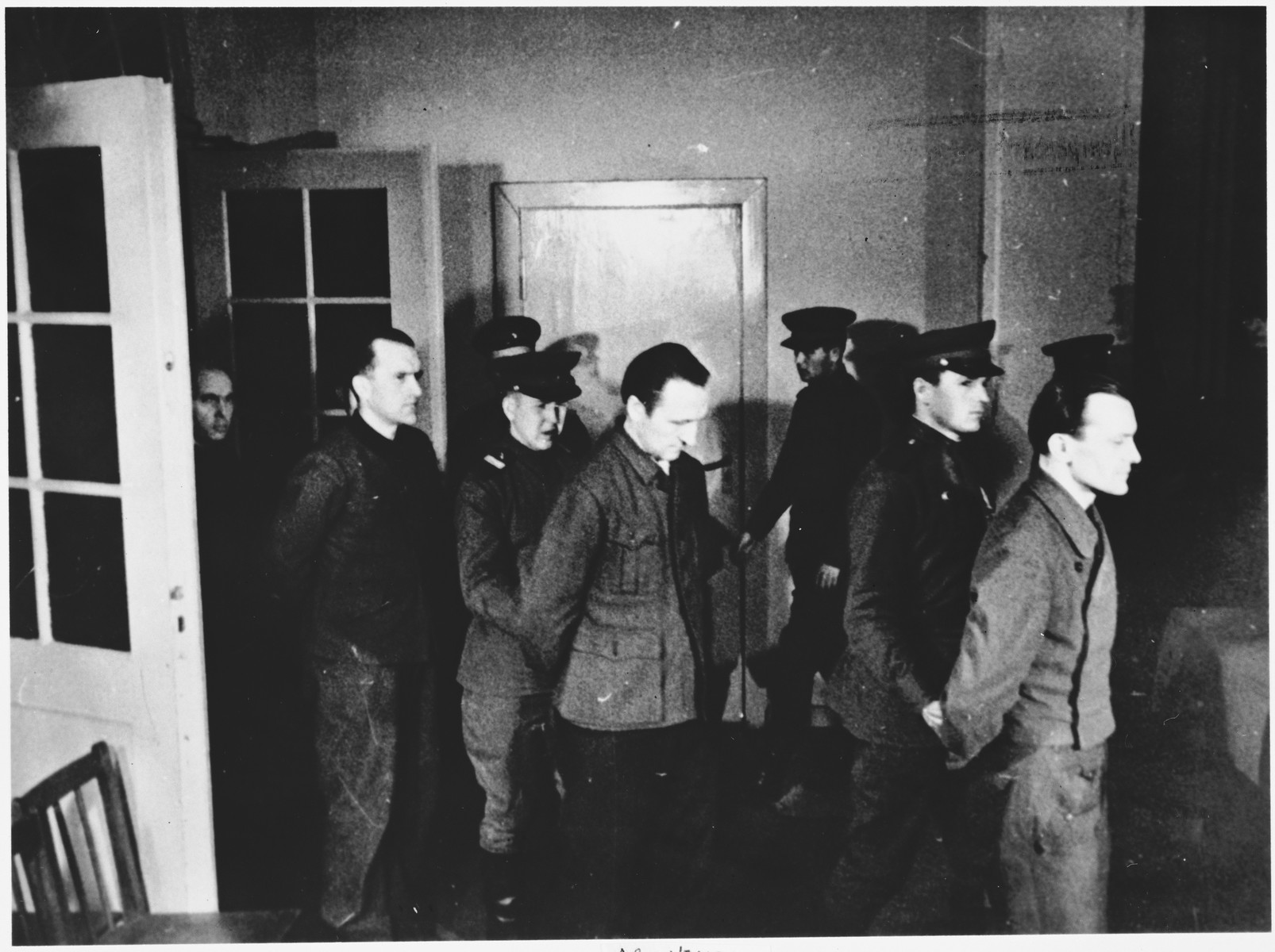 The defendants are led into the courtroom at the Sachsenhausen concentration camp war crimes trial in Berlin.
