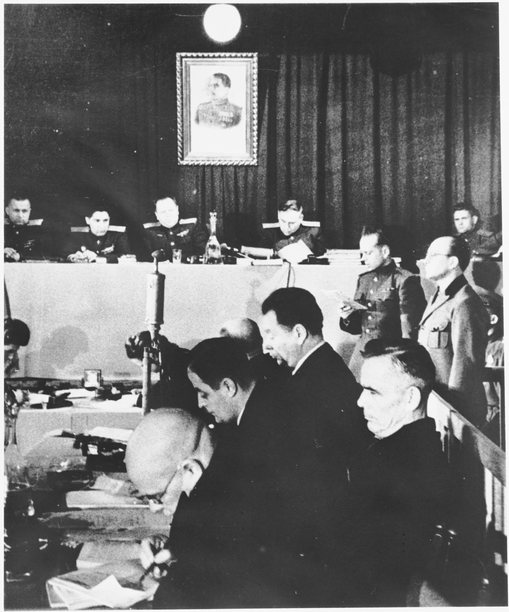 Defendant Anton Kaindl (right) stands in the dock at the Sachsenhausen concentration camp war crimes trial in Berlin.