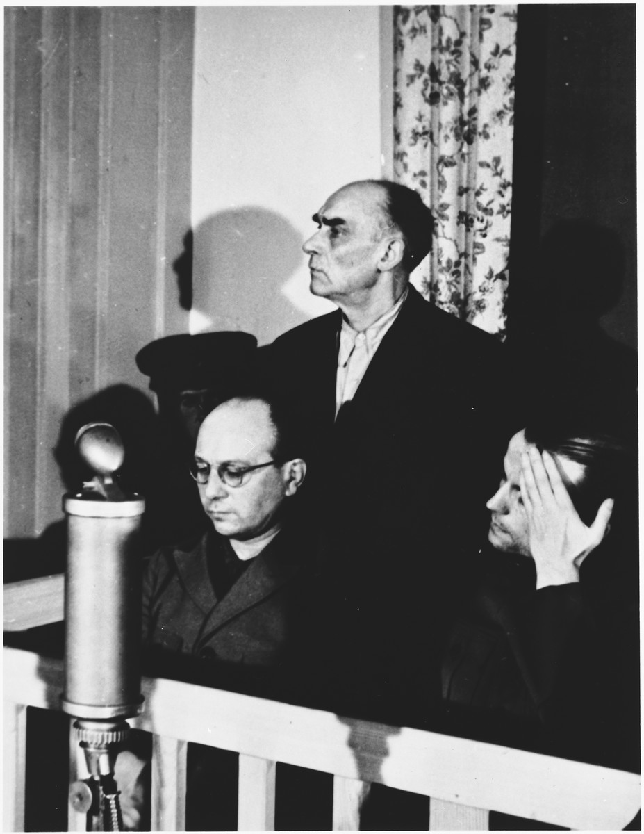 Defendant Karl Zander stands in the dock at the Sachsenhausen concentration camp war crimes trial in Berlin.    In front of him are Anton Kaindl (left) and August Hoehn (right).