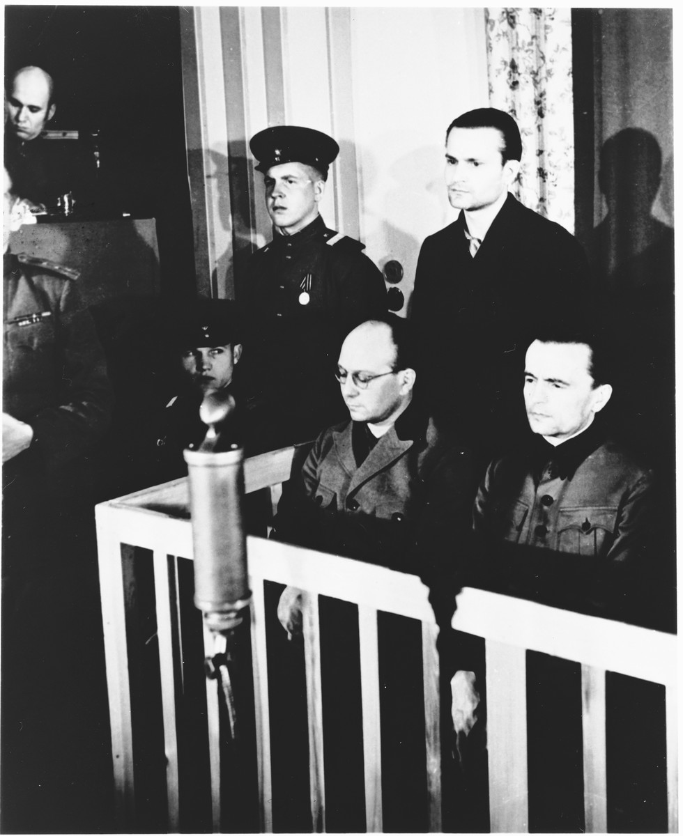 Defendant Paul Sakowski stands in the dock at the Sachsenhausen concentration camp war crimes trial in Berlin.    In front of him are Anton Kaindl (left) and August Hoehn (right).