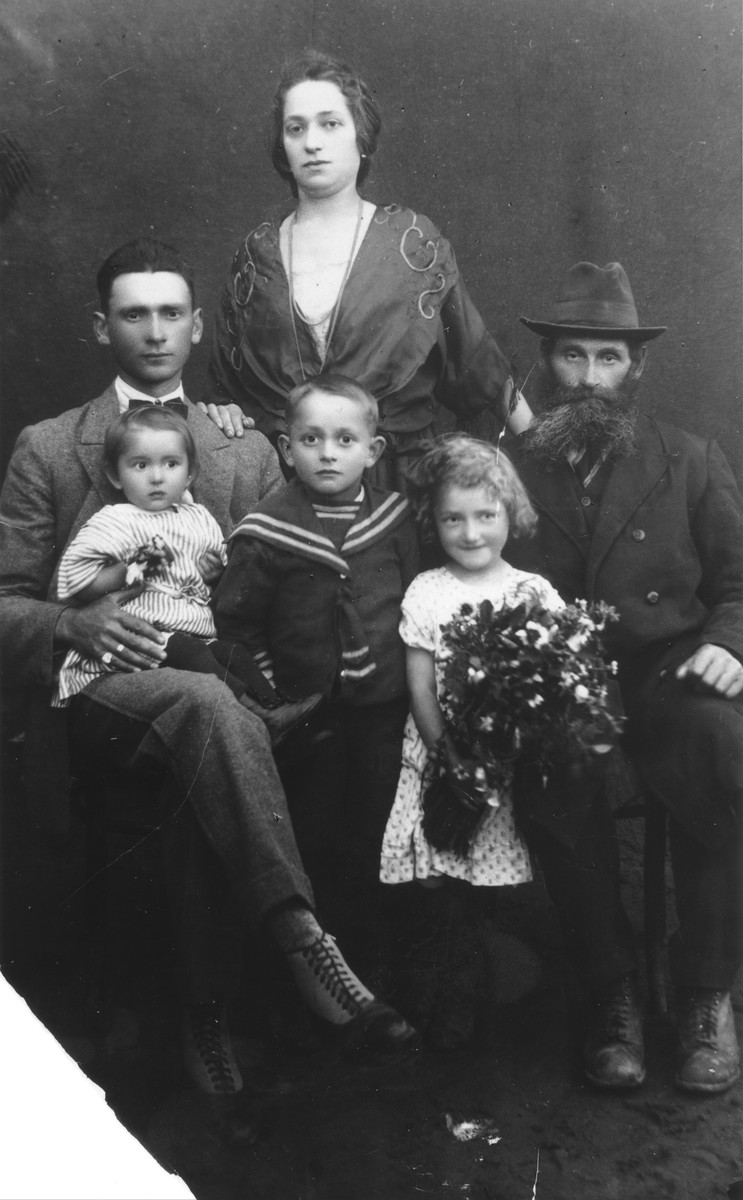 Studio portrait of the Katz family in Vilna.  George Katz (now Crane) stands in the middle surrounded by his parents, grandfather and younger sisters, Lola and Nechama.