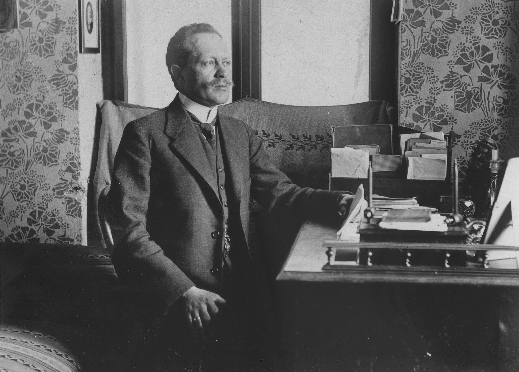Portrait of Dr. Adolf Huber sitting at his desk in his medical office.