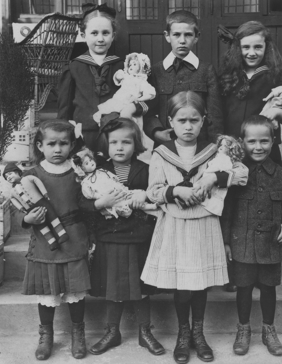 A group of young Jewish children pose with their dolls.  Among those pictured is Irenka Huber (top left) and Eliska Huber (top right).