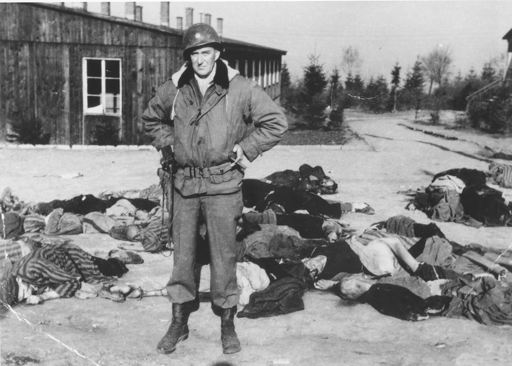 An American soldier stands in front of a large number of corpses that are strewn along the road in the newly liberated Ohrdruf concentration camp.