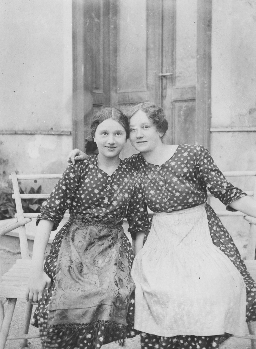 Two sisters pose on a wooden bench outside their home.  Pictured are Eliska (left) and Irenka Huber.
