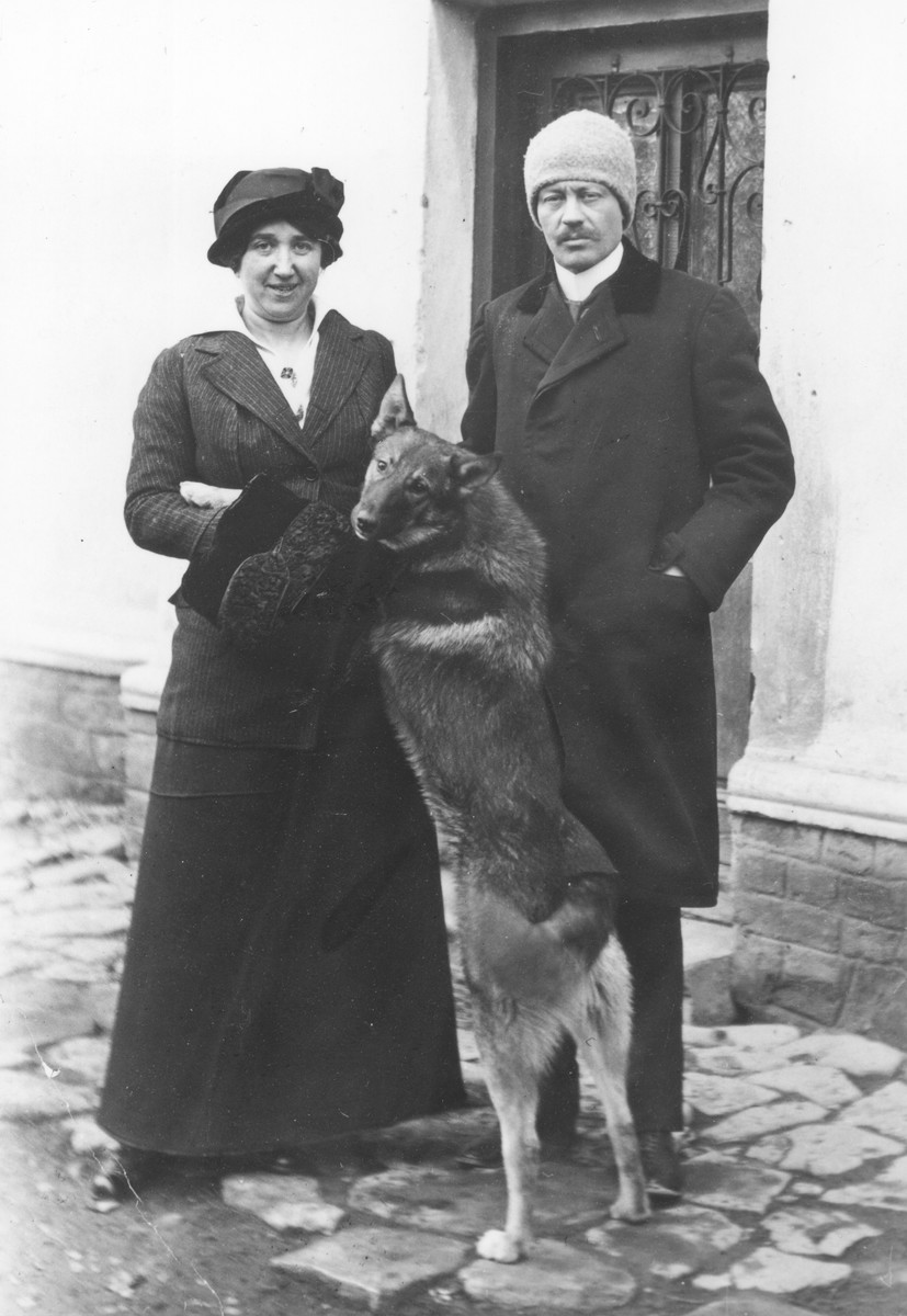 Dr. Adolf Huber and his wife Paola Huberova stand with their dog outside their home in Stara Tura, Slovakia.