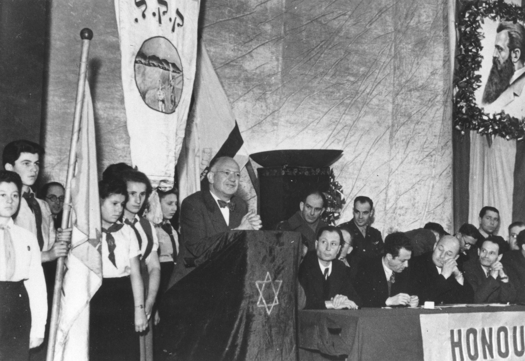 Judge Louis Levinthal, adviser on Jewish affairs to the commander of US forces in Europe, delivers a speech at the Prinzregenten theater in Munich about the partition of Palestine.  The room in decorated with a portrait of Theodore Herzl and a banner of the Jewish National Fund (Keren Kayemet).