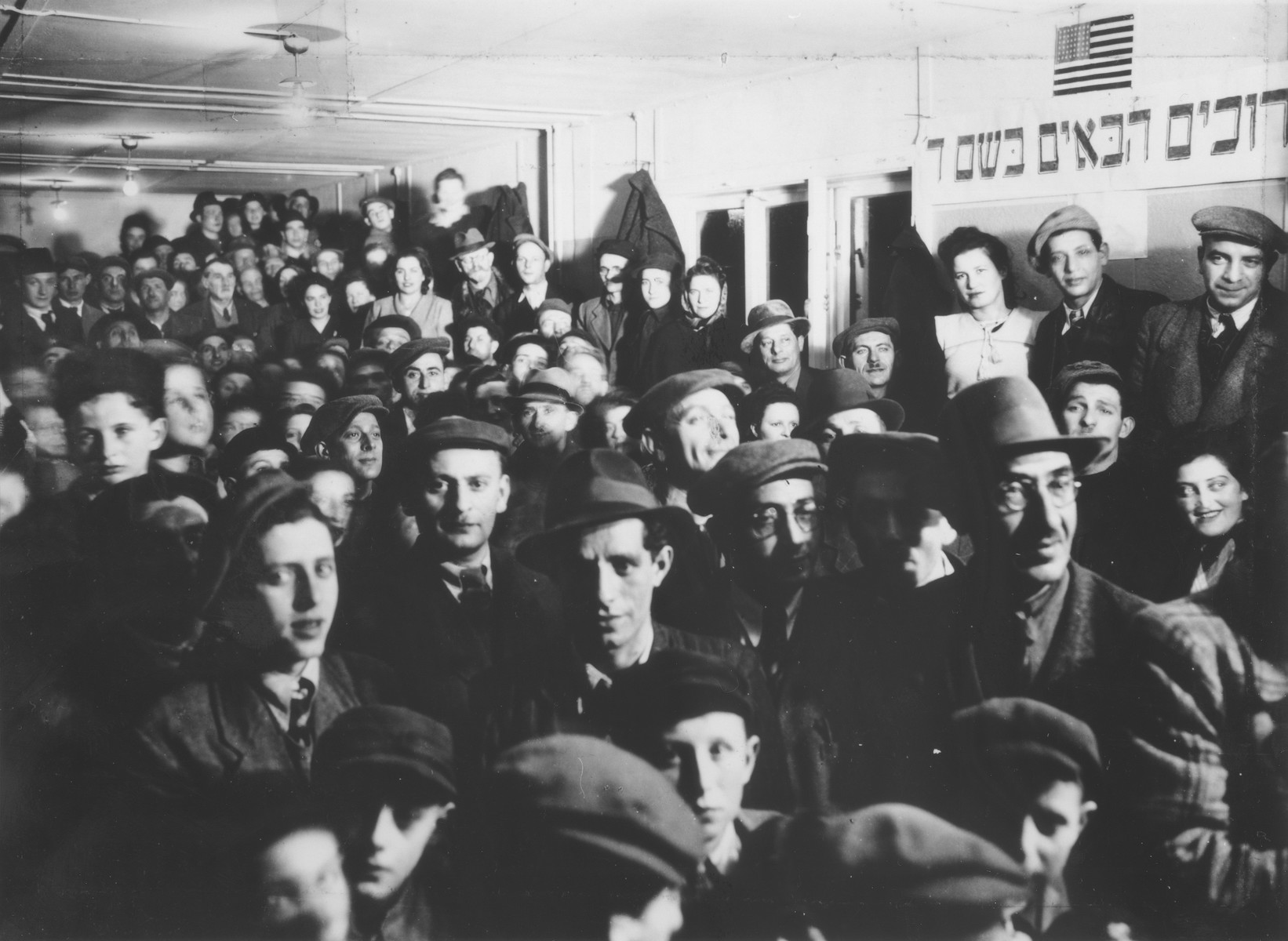 "DPs gather for the opening of the synagogue at the Schlachtensee displaced persons camp.  The Hebrew sign reads, ""Welcome in the name of God."""