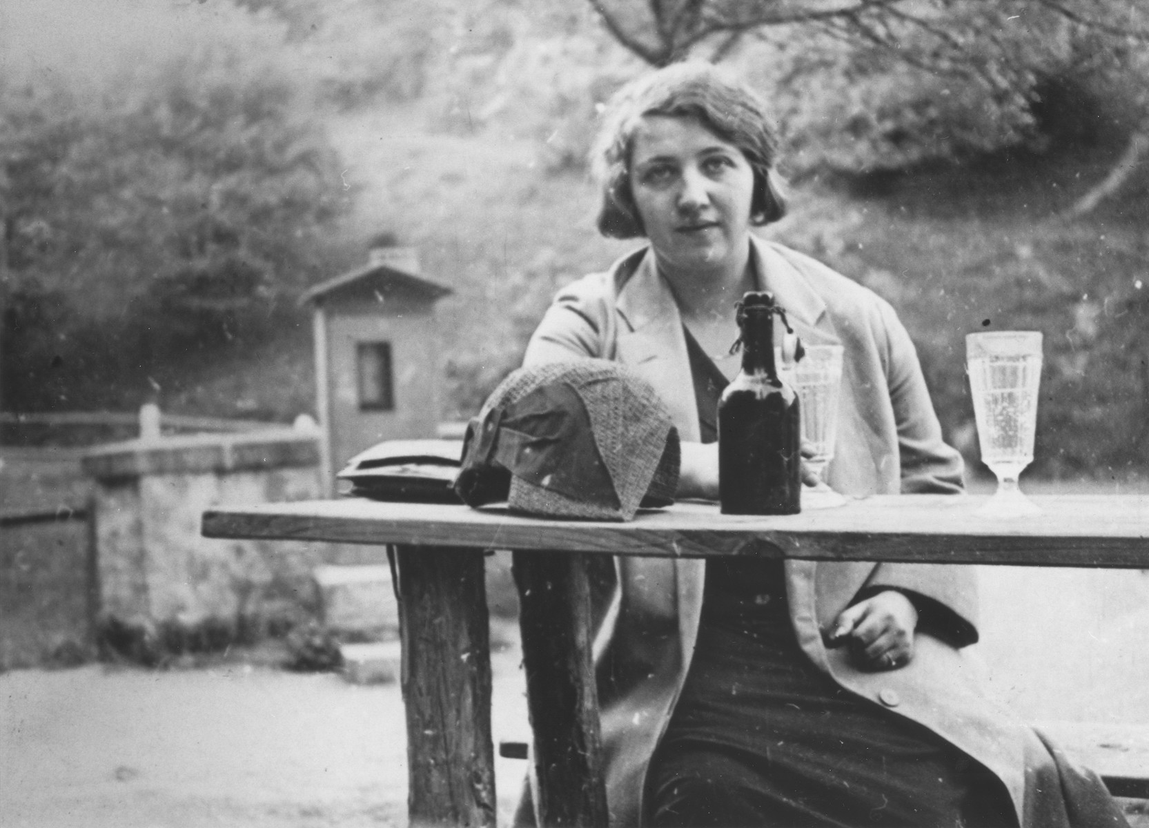 Greta Mayer sits at an outdoor table set with a loaf of bread and a bottle of wine.