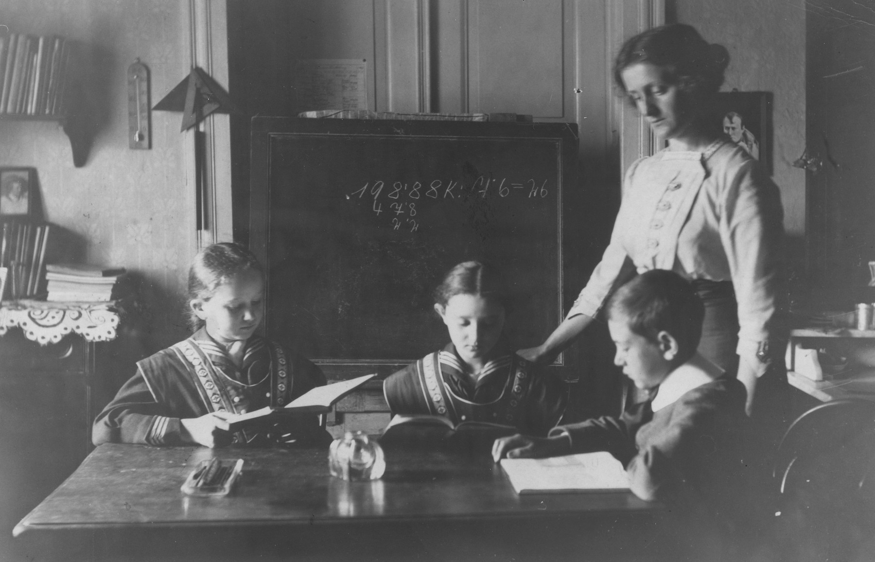 A teacher assists three children with their lessons.  Seated on the far left is Irenka Huber.  Irenka, the sister of Eliska (Huberova) Deutschova, survived WWII in hiding in Hungary.