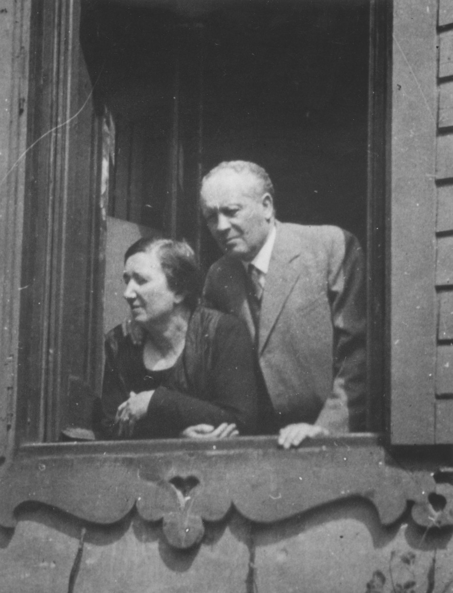 Dr. Adolf and Paula Huber look out the window of their home.