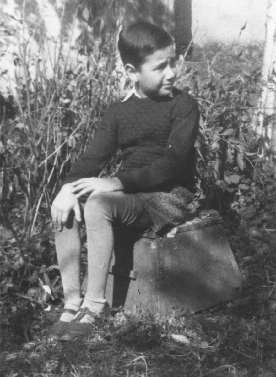 Portrait of nine-year-old Bedrich Deutsch sitting outside in a field in the Uhersky Brod ghetto.