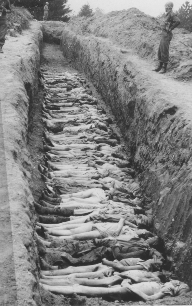 American soldiers stand guard along the perimeter of an open mass grave at Mauthausen.