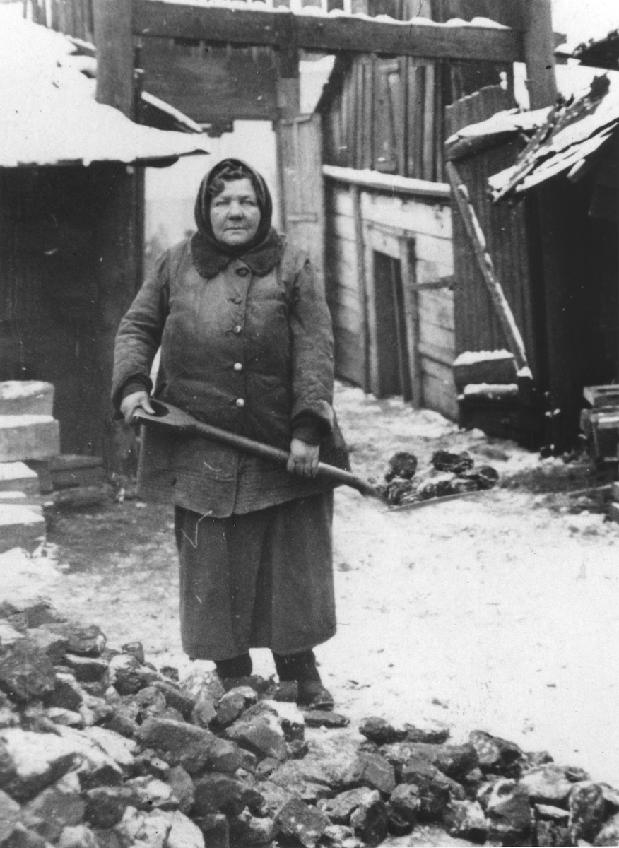 Basia Minc shovels coal in the Minc lumber yard in Vilna [probably during the Soviet occupation].
